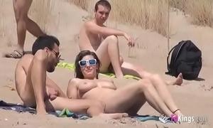 This babe copulates a panhandler in a beach copious voyeurs